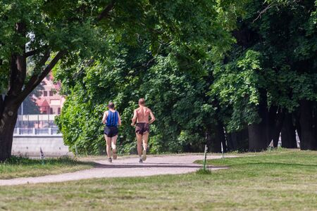 two middle-aged men jogging along the path of the park on a sunny summer morning. Elagin island - morning run in the park