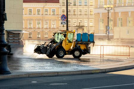 Yellow city car-tractor cleans and washes the street from dirt with water jets