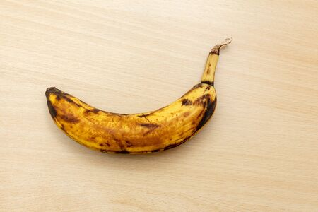 Una singola banana nera viziata su un tavolo di legno