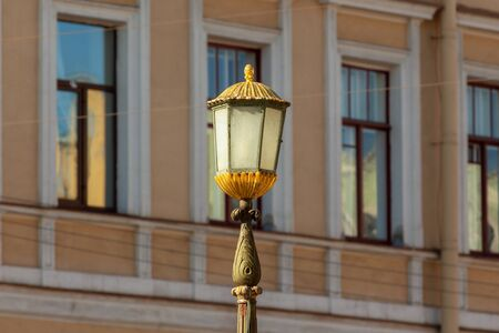 gilded elegant vintage street lamp on the background of windows