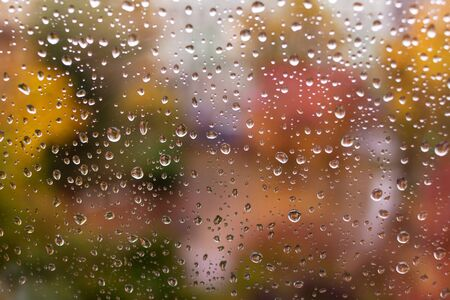 Raindrops on a window pane. Colorful autumn abstract background in soft colors. moody rainy weather