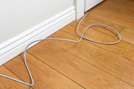 cordon de raccordement sur le parquet de la pièce le long du mur. câblage internet inconfortable dans l'appartement. Avantages et facilité d'utilisation de la technologie sans fil Banque d'images