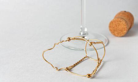 gelbes drahtgeflochtenes Muselet mit Sektkorken und Weinglas auf hellem Hintergrund