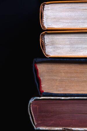 Pila di 4 vecchi libri con copertina rigida polverosi su uno sfondo scuro. Il concetto di letteratura e conoscenza