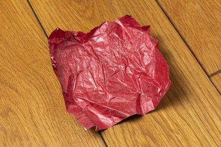 red crumpled candy wrapper on a wooden floor