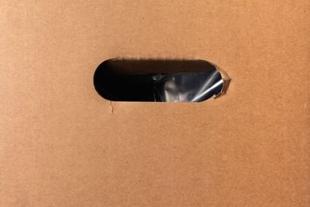 oval hole in the wall of a cardboard box for manual carrying. close-up. goods delivery