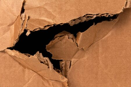 damaged cardboard box with a black hole. damage in the delivery of parcels and shipments