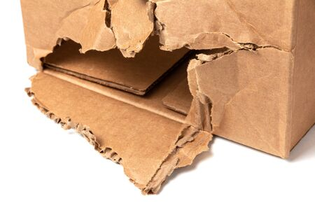 Torn cardboard box with a big hole. Loss and damage insurance concept Reklamní fotografie