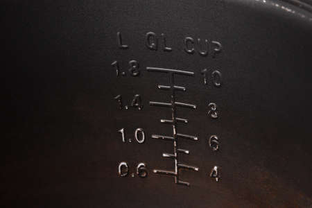 Measuring scale for ingredients on a dark wall of a metal pot of a multicooker.