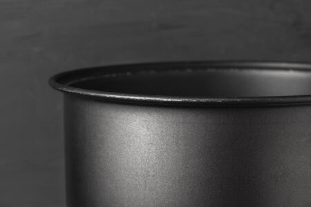 The edge of a titanium mug or pan close-up on a gray background. Minimalism in tourism. Modern kitchen utensils