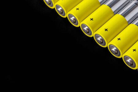 A row of gray-yellow AA alkaline batteries on a black background. Use and disposal of NiMH batteries. Copy space. Stock Photo
