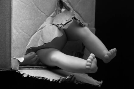 The feet of a childrens plastic doll stick out from a torn cardboard box on a dark background.