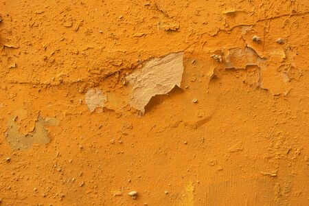 old cracked and dilapidated wall covered with bright yellow plaster