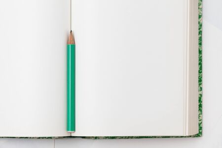 An open notebook with blank white pages and a pencil for notes. View from above. Minimalistic style