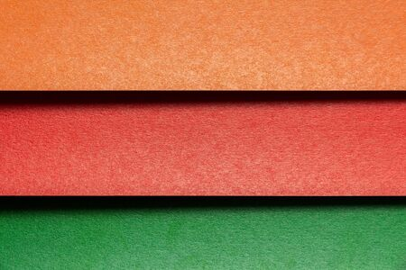 three color sheets of cardboard in the form of blinds: red, brown and green