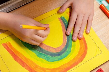 Hands of a child painting a rainbow on a sheet of paper at a desk