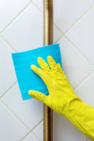 Wipe the brass toilet flush pipe with a yellow gloved hand from dirt and dust