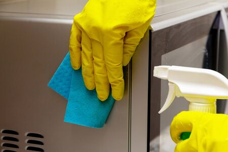 Woman hands in rubber gloves washing microwave from dirt and dust. Kitchen and apartment cleaning 版權商用圖片