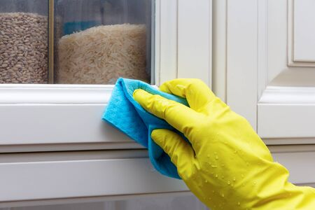 Cleaning and wiping the doors of the facade of the kitchen cabinet. Hand in a yellow glove with a blue rag