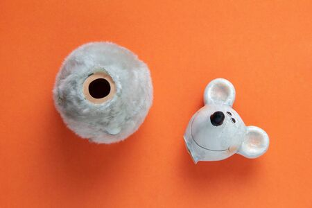 broken ceramic figure of a rat or mouse on an orange background. Head apart from the body 版權商用圖片