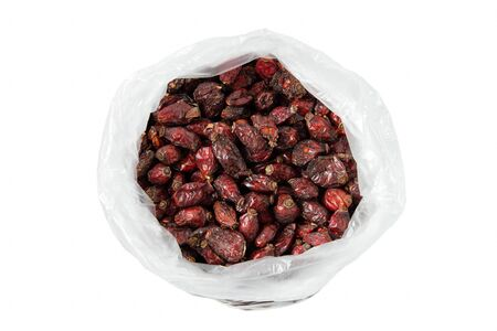 dried rosehip berries in an open cellophane bag on a white background 版權商用圖片