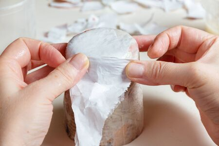 Female hands glue a glass with scraps of paper in the process of creating paper mache