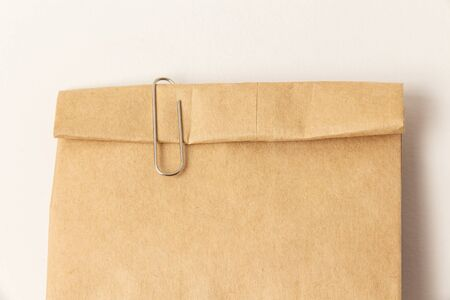 A paper clip on a closed paper bag. Close-up