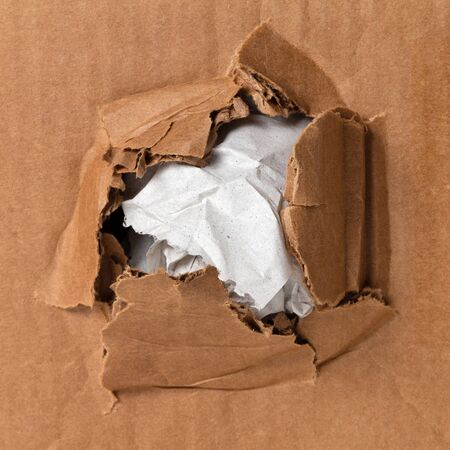 Crumpled wrapping paper sticks out of a hole in a damaged cardboard box. Damage insurance concept for online shopping and delivery
