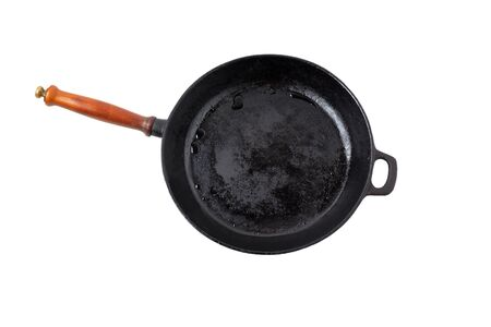 Empty washed black cast-iron frying pan with wooden handle and drops of water