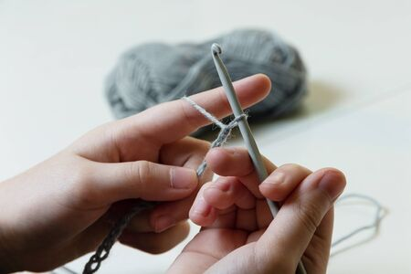 Girl learning to crochet. Knitting needle and woolen thread in children's hands 版權商用圖片