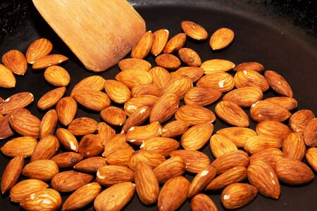 Roasting raw almonds in a pan. cooking food