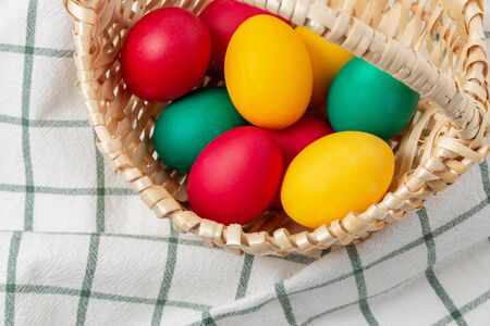 Bright easter colored chicken eggs in a wicker basket. 版權商用圖片
