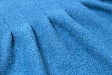 Blue wool texture of a thin Italian pleated coat. Concept of fashion and design as a background or scenery