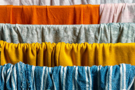 Washed colored textile clothing on the clothes dryer. close up