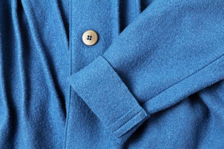 A fragment of the texture of an elegant blue woolen children's coat for girls with a sleeve and a button. The concept of fashion and atelier clothing 版權商用圖片