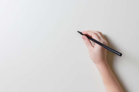 Girls hand with a black marker writes or draws something on an empty clean light wall or board