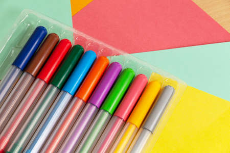 set of multi-colored felt-tip pens on a table with colored sheets of paper 版權商用圖片