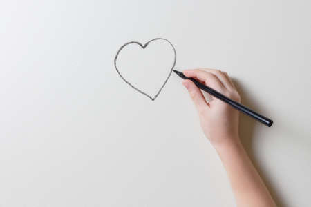 Girl's hand draws a heart on the wall of the room. Minimalistic photo with place for text and design. Life insurance, health and valentine's day concept