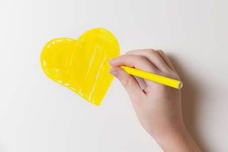 Girl draws a felt-tip pen a yellow heart on the wall of the room. Health and happy childhood concept.