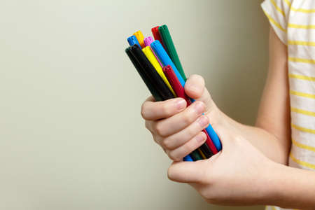 Girl holds several colored markers with both hands. Close up. The concept of home learning and creativity