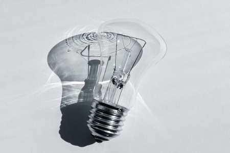 Old incandescent light bulb with a sharp shadow. Minimalistic black and white photo. The concept of development and energy conservation 版權商用圖片