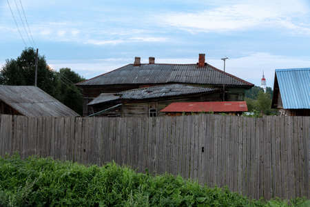 Old rustic abandoned house behind a high wooden fence 版權商用圖片
