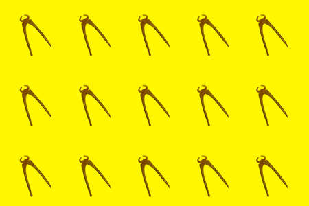 Pattern of large old pliers on a yellow background
