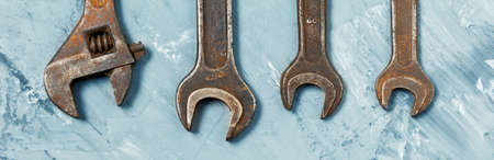 Set of large old wrenches and spanners hanging on the concrete wall of the garage