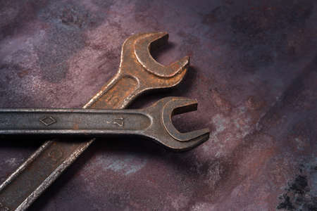 Two large classic old wrenches on a rusty background in a beam of light