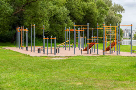 An empty playground with horizontal bars, crossbeams and parallel bars. Outdoor sports in nature in the city green park. Children's game complex
