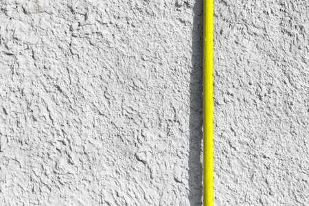 Yellow pipe on gray uneven concrete wall. Minimalistic industrial background with place for text and design on the left side