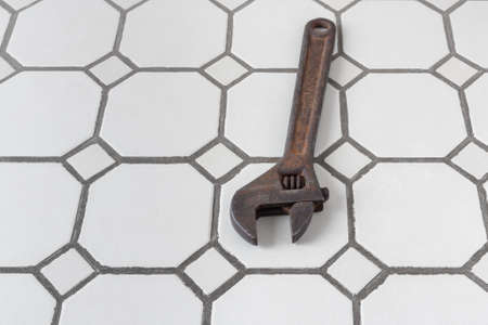 Large adjustable wrench on the tiled bathroom floor