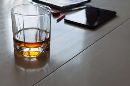 A glass of whiskey on a home kitchen table with a tablet, pencil and book. Remote work at home. Stress and busyness
