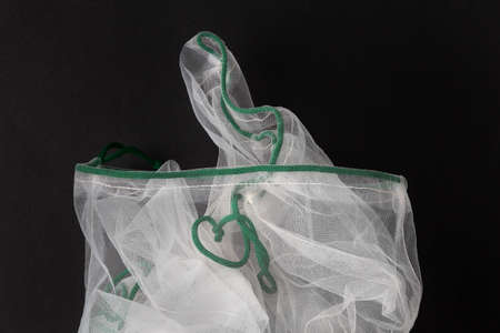 Reusable white mesh nylon grocery bags for vegetables and fruits on a black background